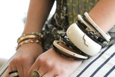 """Catrinel Ardeus, Director of Sales at Monique Péan (hand upward):  Left arm: """"A selection of naturally-shed buffalo horn and fossilized woolly mammoth, with conflict- and devastation-free black and white diamonds and 18-karat recycled rose gold. Also, a combination of vintage ebony and scrimshaw beads with Tahitian pearls and diamond bead bracelets!""""  Right arm: """"Cartier Love bracelet and two bracelets given to me when I was 13 years old. The red Tamy Brand bracelet wards off negative…"""
