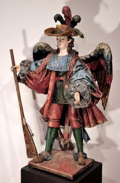 "Bolivian Arcabucero; ca. 1650, wood, gesso, polychrome, and gold, 43"" x 26"" x 20""    An ángel arcabucero is an angel depicted with an arquebus (an early muzzle-loaded firearm) instead of the traditional sward. Arcabuceros were dressed in clothing inspired by that of Spanish aristocrats. The style arose in the Viceroyalty of Peru in the second half of 17th century, right around the time this piece was crafted."
