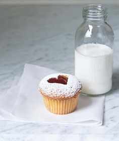 Slice top off cupcake, and use cookie cutter to stamp out favorite shape.  Place spoonful of jelly on each cupcake, then sprinkle tops with powdered sugar.  Reassemble cupcakes.    I think even I could make this.