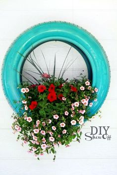 I never thought tires in a garden were attractive however this is pretty! I could imagine this attached to a shed a side fence vertical garden. Love the 'pop' of colour too. @DIY Show Off