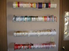 Use plastic rain gutters (comes in 10ft sections, we cut ours into 2 ft. pieces), end caps and braces for your ribbon.  Easy to grab and easy to replace when the bolts run out!