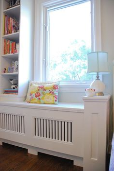 We're loving the way turned an awkward corner radiator into a room focal-point with the addition of a custom slatted window bench and bookcase.