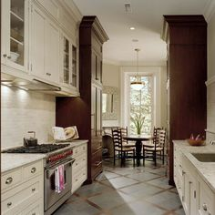 Galley Kitchen two toned cabinets, backsplash, interesting way to bring crown moulding to ceiling