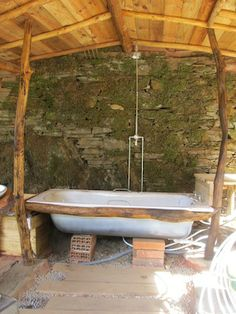 During construction - the original terrace wall, complete with mosses, forms the back wall of the building. Here the bath and shower are being positioned and plumbed in.