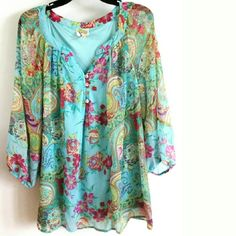 """Fig and Flower 2X Aqua Floral Chiffon Top This beautiful Fig and Flower 2X Aqua Floral Chiffon Top is in great used condition. The body is lined (sleeves unlined) so no need to layer with a cami. Pretty floral & paisley print 100% polyester with shell buttons. Bust: 25"""" across laying flat, measured from pit to pit, so 50"""" around. 30"""" long. ::: Bundle 3+ items from my closet and save 30% off when you use the app's Bundle feature! ::: No trades. Fig and Flower Tops"""