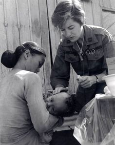 Combat nurse tending to a Vietnamese child.