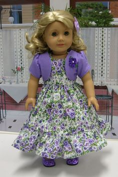 Darling sleeveless dress in a pretty cotton print of purple pansies. The hemline is adorned with a purple pansy cotton ruffle. Bodice is fully lined and fastens in back with buttons and a self tie. Matching short sleeved bolero jacket in purple linen is embellished with a purple ribbon flower on the lapel. Bonus Gift: Metallic purple bow flats and a purple grosgrain ribbon bow with mini bobby pin for a cute hair accessory.    Seams top stitched for durability. No velcro. Other colors or…