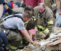 A child is pulled from beneath a collapsed wall at the Plaza Towers Elementary School in following a tornado in Moore, Okla., Monday, May 20, 2013.