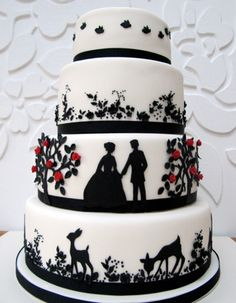 Love the fairy tale silhouette!  Black figures of a bride and groom, deer and other fauna.  black and white cake with red accents