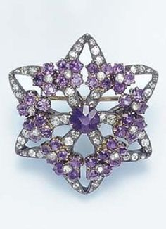 AN ANTIQUE DIAMOND AND AMETHYST BROOCH. Designed as an openwork old European-cut diamond star, enhanced by a circular-cut amethyst and rose-cut diamond flowerhead wreath, centring upon a circular-cut amethyst, mounted in silver and gold, circa 1840, in a Harvey & Gore brown leather retailer's case. #antique #brooch