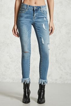 A pair of mid-rise denim ankle jeans featuring a skinny cut, frayed ankle cuffs, a distressed design throughout, five-pocket construction, whiskering at the front.