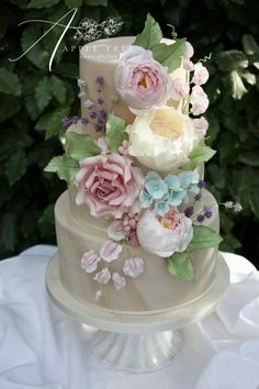 'Melissa' Marble wedding cake decorated with a cascade of handmade sugar flowers: David Austin roses, peonies, hydrangea, sweet pea, lavender and buds, in a beautiful summer colour palette.