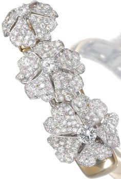 Diamond bangle, Cartier, 1950s. The three flower heads claw-set to the centre with a circular-cut diamond, the petals pavé-set with similarly- and single-cut diamonds, mounted in gold; the flower heads can be detached and worn as brooches, inner circumference approximately 160mm, signed Cartier, Paris and numbered, French assay and maker's marks.