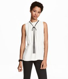 Check this out! Sleeveless blouse in crêped woven fabric. Narrow ruffle trim at neckline, opening at back of neck with button, and elastication at front for a gathered effect. - Visit hm.com to see more.