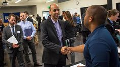 A job seeker (left) shakes hands with a recruiter during a WorkSource Seattle-King County Aerospace, Maritime and Manufacturing job fair in Seattle on Oct. 6, 2015.
