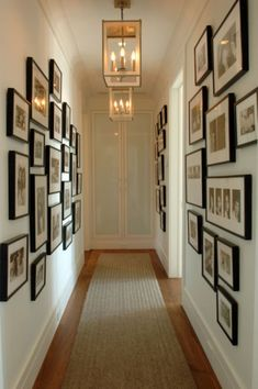 Narrow hallway with black picture frames on the walls.