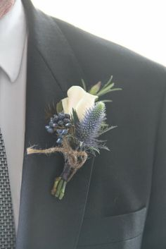 A Beautiful Boutonniere with an Akito Rose, Rosemary, Thistle and Viburnum Tinus, bound with deep blue Ribbon and tied up with earth jute is part of Thistle wedding - Thistle Boutonniere, Thistle Bouquet, Blue Boutonniere, Groomsmen Boutonniere, Groom And Groomsmen, Boutonnieres, Wedding Boutonniere, Bracelet Corsage, Floral Wedding