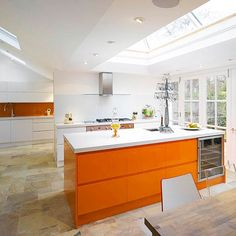 Wow! A pop of vibrant colour is a really winner with this orange island creating a striking focal point in this glass extension.  The matching colourful splashback for a fresh, on-trend look