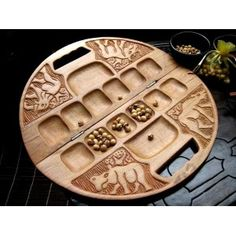 $169.00. A Classic in the mancala family of games. Carved Teak Wood and hand polished. Stunning artwork by skilled artisans. Tthe board comes complete with mative seeds.    Count capture and outplay your opponent!