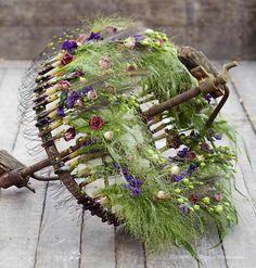 Sébastien Ravot récupère à la campagne un essieu de charrette qu'il fleurit légèrement de lisianthus, pois de senteur, hypericums verts et panicums fountain. Création extraite du Carnet d'Idées #Interflora ! #artfloral #fleurs