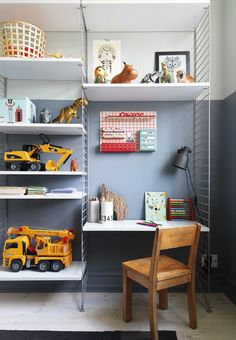Boy kids room with open toy storage and a little reading corner.