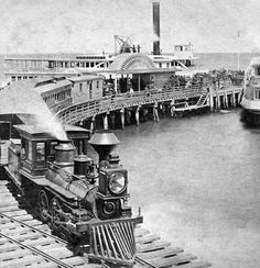 A wood burning steam engine providing passenger service to a Ferry Company pier loading / unloading area
