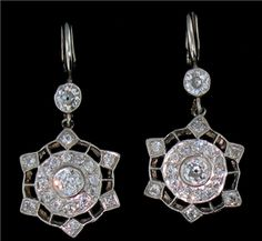 Intricate 18 karat white gold and platinum filigree drop earrings are set with old European cut diamonds