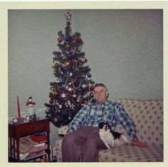 A man and his pet sitting by the Christmas tree.