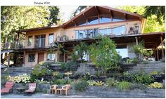 Now we are standing on the pool deck looking at the backside of the two level home in all its Glory....There are wild roses, Clematice, Hastas, lots of other flowers on the hillside....