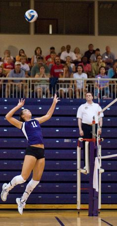 A woman right about to hit the ball during a volleyball game. dude! she even has #11..Yeaah!!