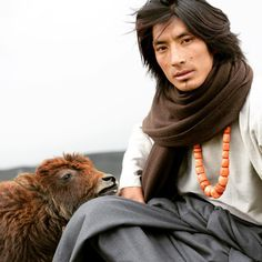 Wangdi, head of the Norlha dyeing section, with baby yak in a Nomad Brown Nets, 100% yak khullu scarf