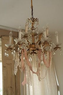 Ribbons and lace swags from chandelier. This looks like something from Miss Havisham's in Great Expectations.