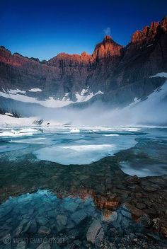 Foggy morning at Iceberg Lake. Glacier National Park, Montana, USA. Iceberg Lake is located in Glacier National Park, in the U. S. state of Montana. Mount Wilbur is south and Iceberg Peak is west of Iceberg Lake. Iceberg Peak towers more than 3,000 feet above the lake