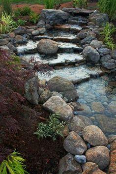 cascade en escalier avec gros cailloux dans jardin