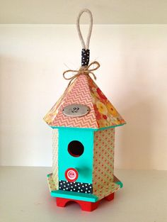 Dollar-store plain wood birdhouse decoupaged with scrapbook papers and craft paint, li'l bit o' twine, house number and washi tape and it's done.