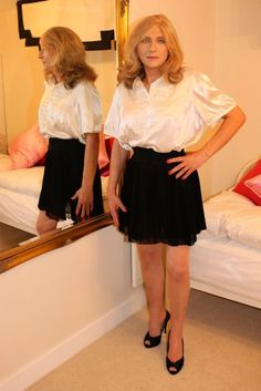 Tina in a cream satin blouse with black chiffon pleated skirt any girl would be proud to wear at the crossdressing service