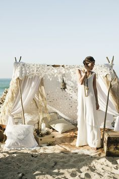 Bohemian Beach. Great set up, but I don't expect anyone to set up camp like this for a regular beach visit. Useful decorating ideas for a beach wedding or high end beach party.