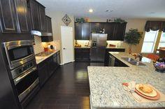 Dark kitchen cabinets and light granite countertop