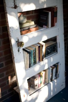DIY bookshelf from old panel doors @ Do It Yourself Pins.  You can see the wood shelves behind this old door, it creates a shabby chic look.  What a great idea for a bookshelf.