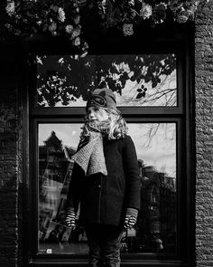 My beautiful girl in Amsterdam. The city reflection in the window the flowers hanging over her the striped gloves and the super hero mask hat. Could I have put more contrasty details in that picture? Thats one of the many beauties of beauties of black and white I find. #whpblackandwhite  Amsterdam is beautiful as always but boy its bloody freezing!! Despite being used to Swedish weather we are just running into cafes before the wind transforms us into ice cubes... at least the sun is…