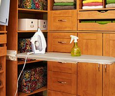 Clever Ironing Board  This built-in ironing board saves floor space and stows vertically between cabinet units. Shelves nearby keep an iron, water mister, and linen spray handy.