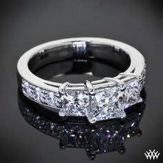Set in Platinum, this gorgeous Custom 3 Stone Diamond Engagement Ring blends a cathedral style shank with an integrated basket head. Brilliant bead set A CUT ABOVE® Hearts and Arrows Diamond Melee lead you to 2 0.50ct A CUT ABOVE® Princess Diamond side stones and a 1.00ct A CUT ABOVE® Princess Diamond in the center.