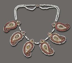 Persia   Necklace composed of a series of six vari-cut ruby and diamond paisley plaques, each centering upon a foil-backed pear-shaped emerald or simulated emerald accent, enhanced by cabochon emerald and seed pearl trim, joined by pearl spacers, to the two-strand pearl backchain, and clasp of similar design, mounted in gold   ca. mid to late 19th century
