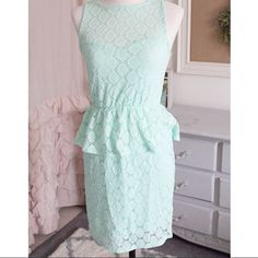 Mint Crochet Peplum Dress The perfect and most flattering dress! It has a form fitting under layer with the beautiful crochet overlay. New without tags! This classy sleeveless short dress features an eyelet patterned fabric with peplum waistline. Partially lined. 96% nylon. 4% spandex. Super flattering!! Everly Dresses