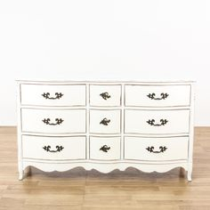 This french provincial dresser is featured in a solid wood with a distressed white paint finish. This long dresser has 9 drawers, a curved serpentine front and metal acanthus leaf handles. Cottage chic storage piece perfect for brightening up a room! #shabbychic #dressers #longdresser #sandiegovintage #vintagefurniture