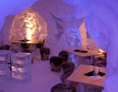 This extravagant ice hotel has an igloo aesthetic, wooden furniture, animal skin throws, subtle lighting, and faces carved into the ice.