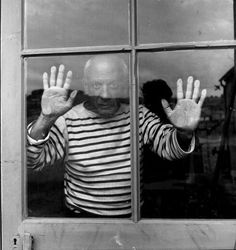 Pablo Picasso behind a window, 1952, by Robert Doisneau