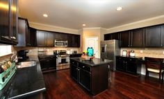 This spacious kitchen from @Lennar Raleigh features beautiful dark cabinets and a great island!