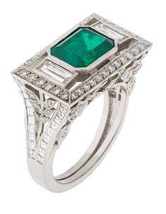 AN ART DECO EMERALD AND DIAMOND RING Collet-set with a principal emerald-cut emerald and two baguette-cut diamonds, within a frame of millegrain-set circular-cut diamonds, pierced foliate mount of circular-cut diamonds and pavé-set with calibré-cut diamonds, circa 1930