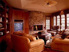 wall colors, comfy leather furniture in color, windows, stone fireplace and hearth, stepped ceiling with lighting
